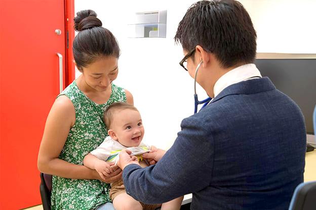 お母さんと笑顔で診療を受けている赤ちゃん