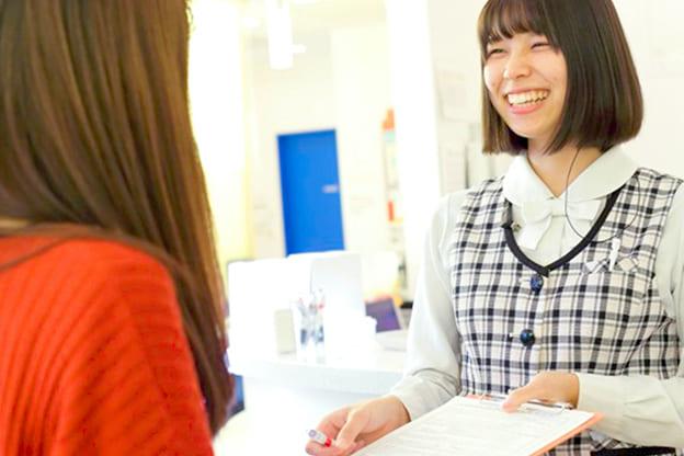 患者さんと笑顔で会話するクリニックの受付女性