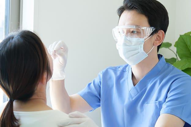 女性患者に対して医師がPCR検査を行っている様子