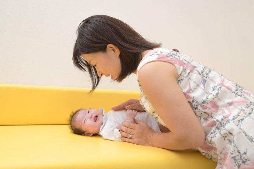 横になっている赤ちゃんをあやしているお母さん