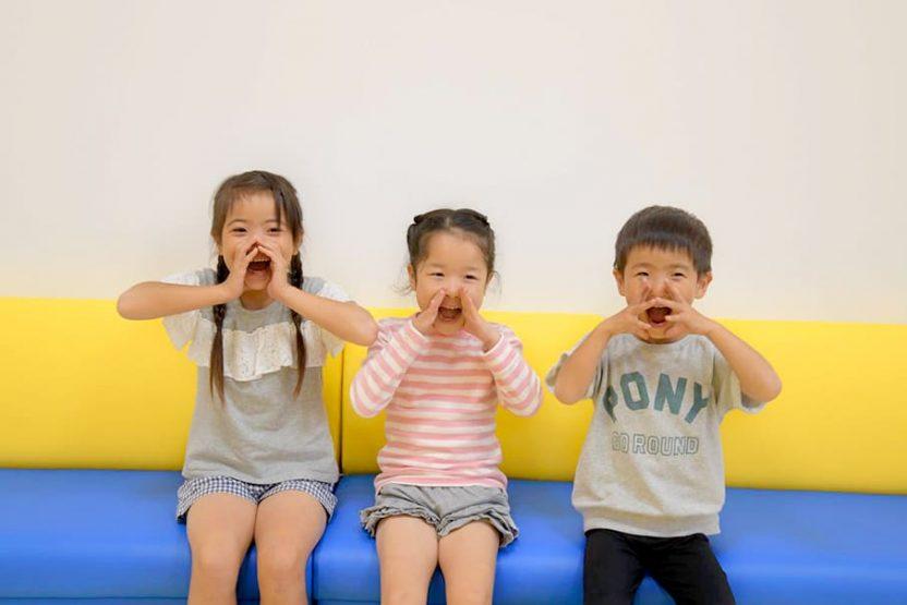両手を口元にあて、叫んでいる仕草の3人の子供